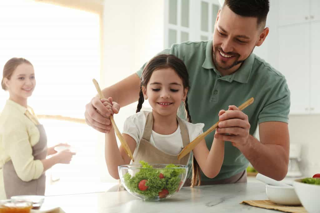 Father and daughter enjoying mixing a bowl of salad with the mother watching at the back.